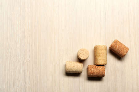 Five wine corks on light wooden background