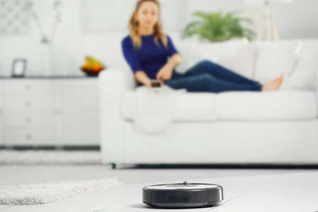 Robotic vacuum cleaner cleaning the room while woman resting on sofa