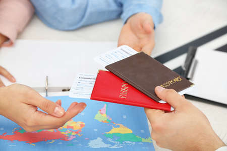 Agent giving passports and tickets to customers in the office of travel company Фото со стока