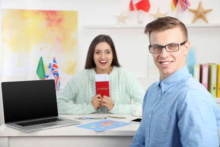 Agent and happy young woman with passport and ticket in the office of travel company