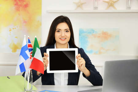 Young woman holding tablet in the office of travel company Stock Photo