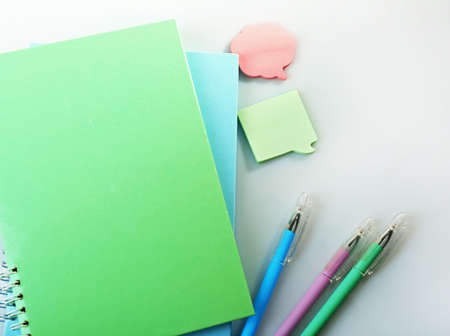 A pile of notebooks and stationary, isolated on white background