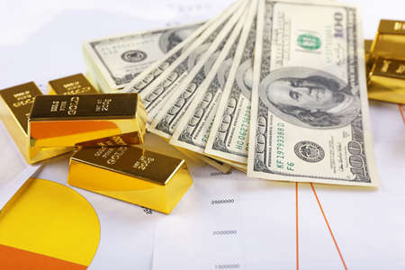 Gold bars with dollar banknotes on paper background Stock Photo