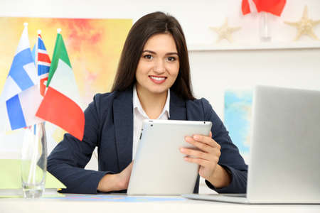 Young woman using tablet in the office of travel company Stock Photo