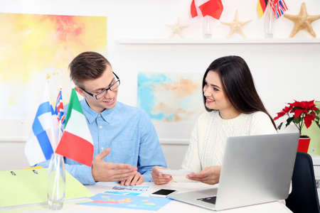 Agent offering vacation options for young woman in the office of travel company