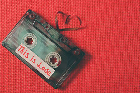 Retro audio cassette with tape in shape of heart on red fabric background