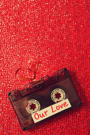 Retro audio cassette with tape in shape of heart on red textured background