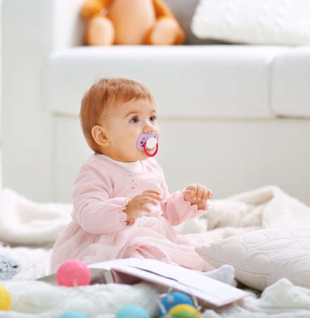 Sweet baby girl with a soother playing on floor