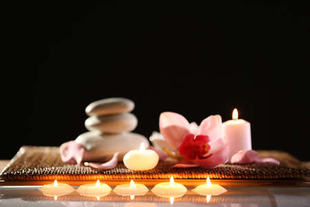 spa still life with stones candles and flowers in water on black