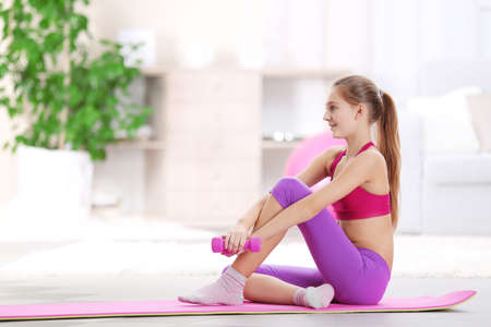 Young girl making fitness exercise indoors Archivio Fotografico