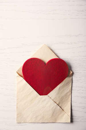 Blank open envelope with heart on wooden background
