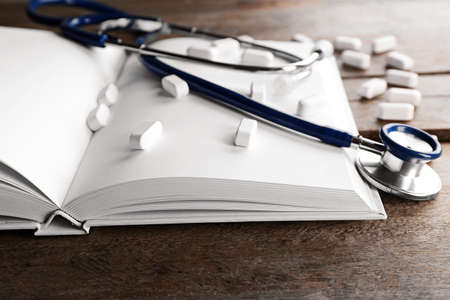 Stethoscope with open book and pills on wooden background. Medical literature concept Stock Photo