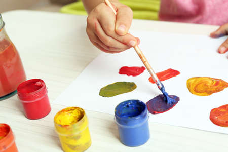 Child drawing with bright paints on paper, closeup Stock Photo