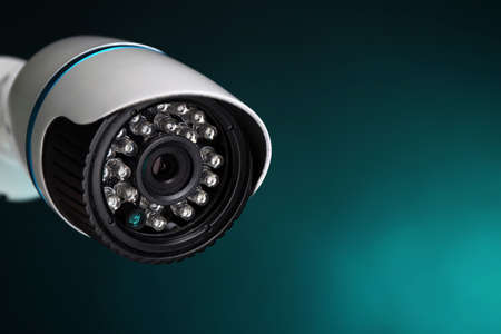 Security CCTV camera on blue background, closeup Stock Photo