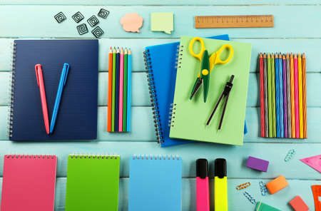 School set with notebooks, scissors and colored pencils on wooden blue background Stockfoto