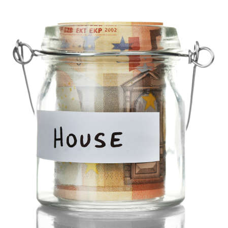 Glass jar with euro banknotes for  house, isolated on white