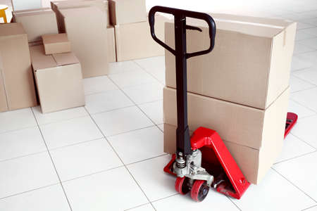 Fork pallet truck with stack of cardboard boxes indoors Stock Photo