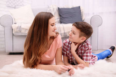 Mother and son lying on the carpet beside sofa in the room Stock Photo