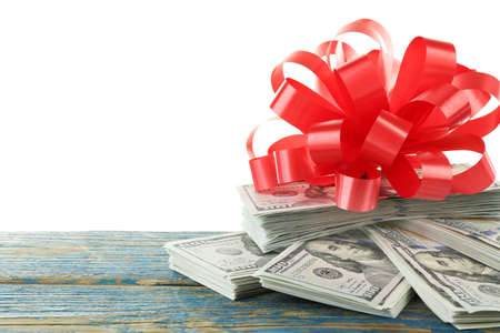 Pile of dollars with bow as gift isolated on white Stock Photo
