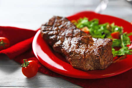 Grilled steak with vegetable salad, closeup