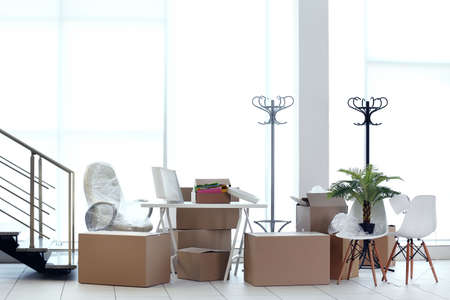Moving cardboard boxes and personal belongings near stairs in office Stock Photo