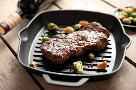 Grilled steak on grill pan with wine on wooden table Reklamní fotografie