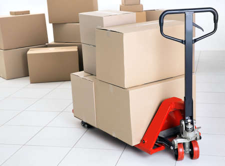 Manual pallet truck with carton boxes indoors Stock Photo