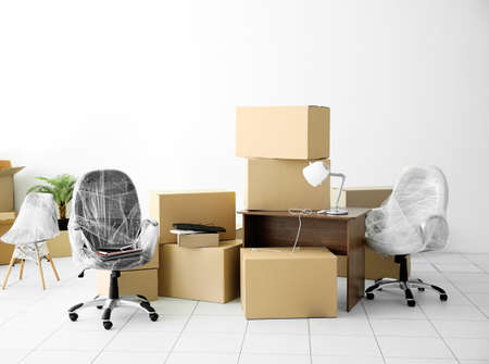 Moving cardboard boxes and personal belongings in empty office space Foto de archivo
