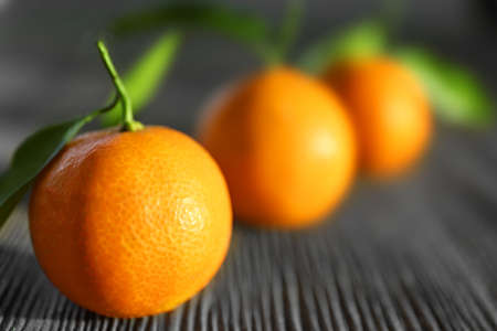 Fresh tangerines with leaves on wooden table, closeup Stock Photo