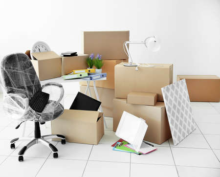 Moving cardboard boxes and personal belongings in empty office space Stock Photo
