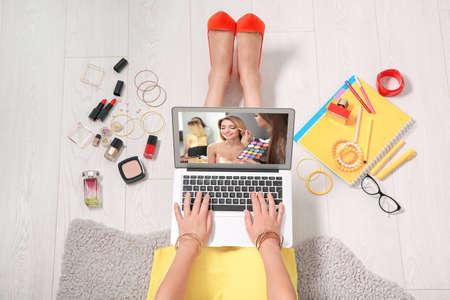 Mujer sentada en el piso con una computadora portátil y viendo capacitación en línea para maquilladores profesionales