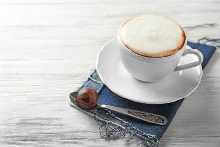 Cup of hot cappuccino with froth and candy on white wooden table table Stock Photo