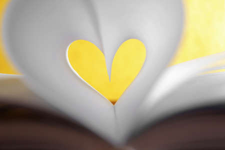 Heart from book pages on yellow blurred background Stock fotó