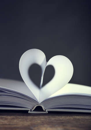 Heart from book pages on dark blurred background Stock fotó