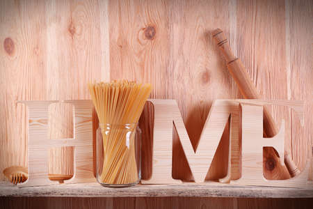 Home word with rolling pin and spaghetti on wooden background Archivio Fotografico