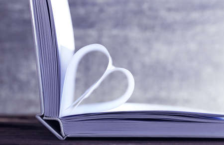 Heart from book pages on grey blurred background