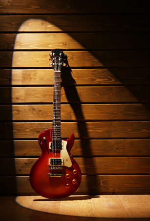 Electric guitar on dark lighted wooden background