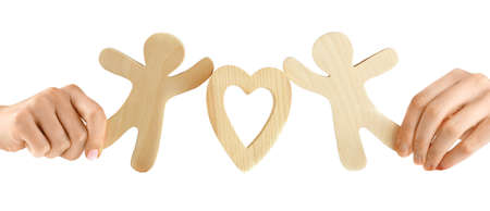 Hands holding a couple of wooden figures with heart, isolated on white