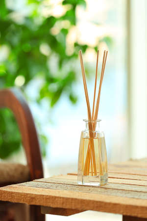 Handmade reed freshener on wooden table in living room, close up Stock Photo