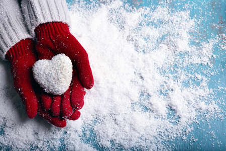 Het wijfje dient vuisthandschoenen met decoratief hart op sneeuwachtergrond in