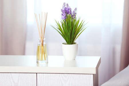 Handgemachter Reederfrischer mit Blume auf weißer Kommode im Wohnzimmer, Abschluss oben
