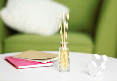 Handmade reed freshener with notebooks on white table in living room, close up Stock Photo