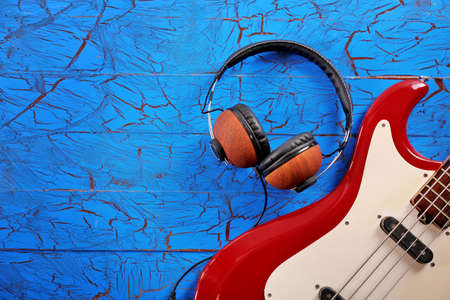 Electric guitar with headphones on blue wooden background Stock Photo