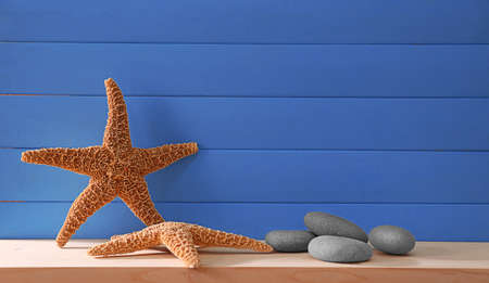Starfishes with pebbles on blue wooden background Stock Photo