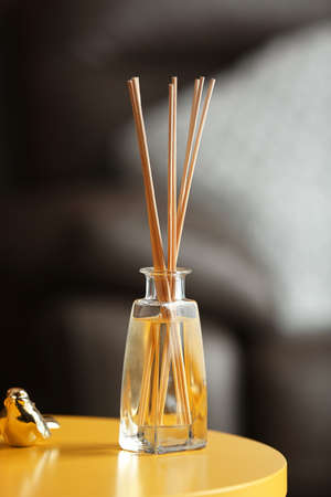 Handmade reed freshener on yellow table in living room, close up