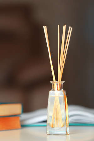 Handmade reed freshener with books on white table in living room, close up Stock Photo