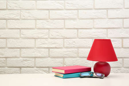 Night lamp and home decor on the desk on brick wall background Imagens