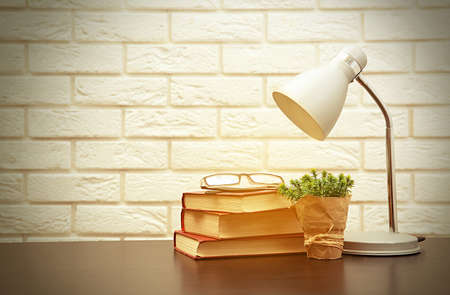 Modern lamp and books on the desk on white wall background Stok Fotoğraf