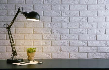 Lampa i rośliny na biurku na tle ściany