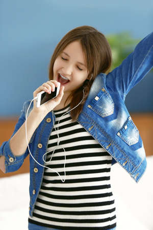 Happy girl listen to music and singing into mobile indoor